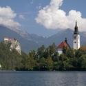 Kostel na Bledském jezeře v pozadí s hradem lemovaným horskými štíty ve Slovinsku.