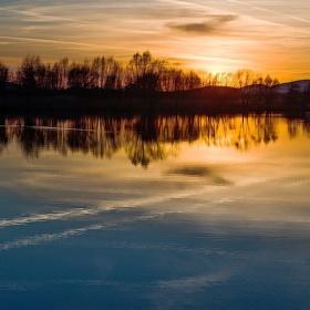 Slunce zapadá nad rybníkem