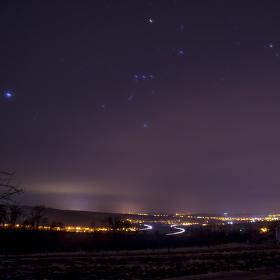 krátká stopa Orionu nad osvětleným krajem...