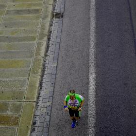 Osamělý běžec důchodové věku ve městě po dešti