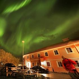 užaslý fotograf sleduje polární záři na parkovišti před hotelem