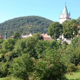 Město Tišnov, zarostlé v zeleni s horou Květnici.