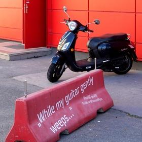 Červená zeď s motocyklem a vzpomínkou na Beatles