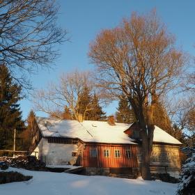 Zimní chata při západu slunce.