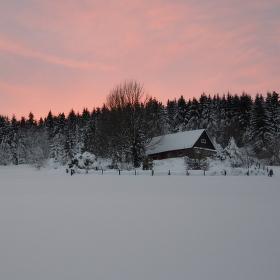 Opuštěná a zapadaná chata ve vrcholící zimě.