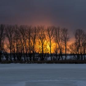 Západ slunce nad zamrzlým rybníkem
