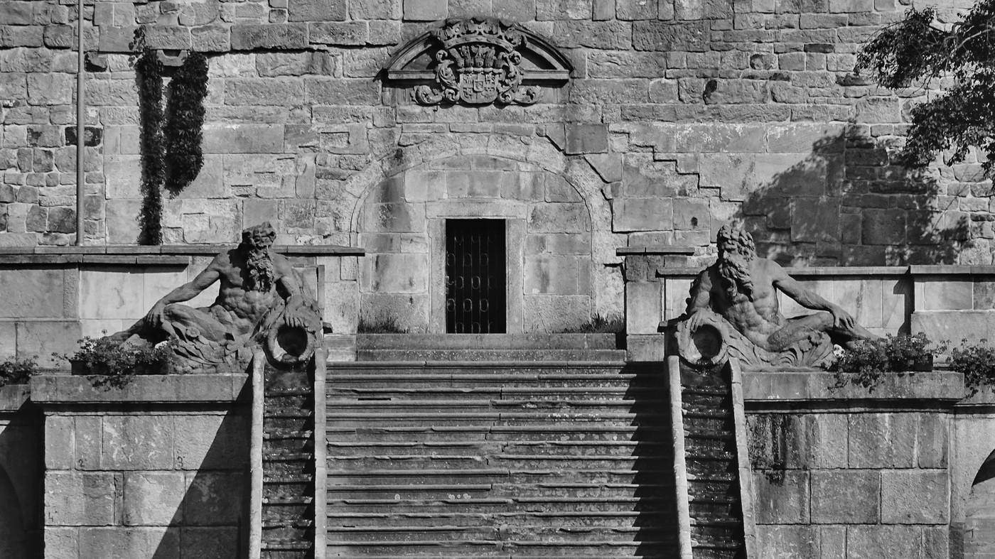Barokní zídka s plastickým Šporkovým erbem a kaskádové schodiště se dvěma sochami tritonů.