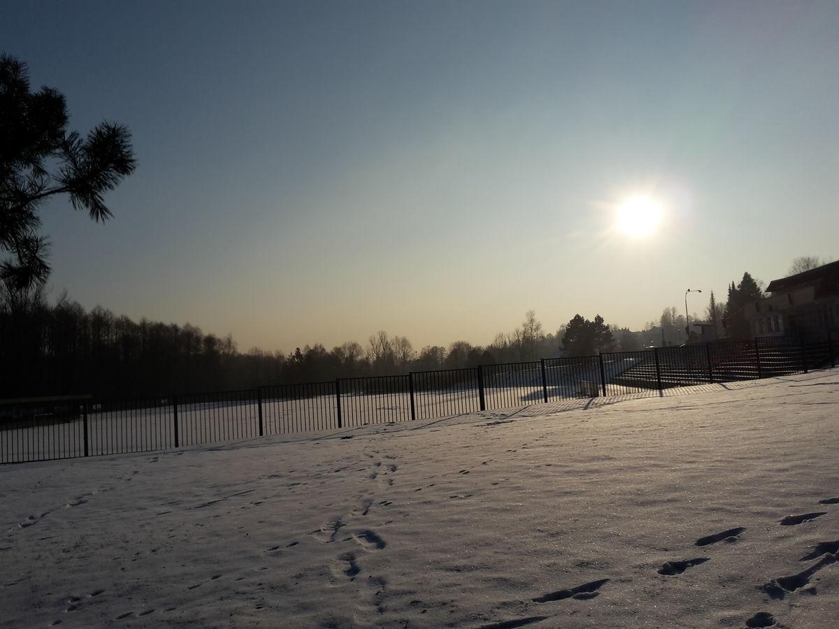 Západ slunce nad zasněženým hřištěm