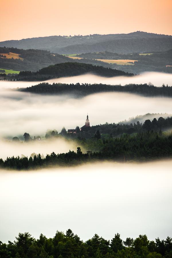 V mlhách