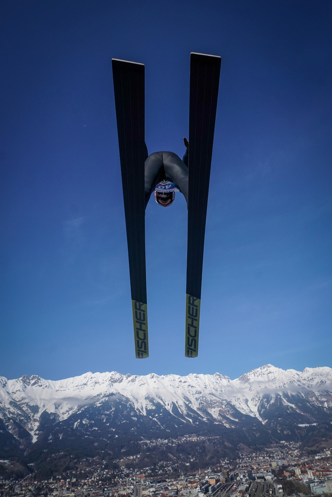 tomasz-markowski-sony-alpha-9-looking-up-at-a-ski-jumper-as-he-passes-overhead-against-a-deep-blue-sky