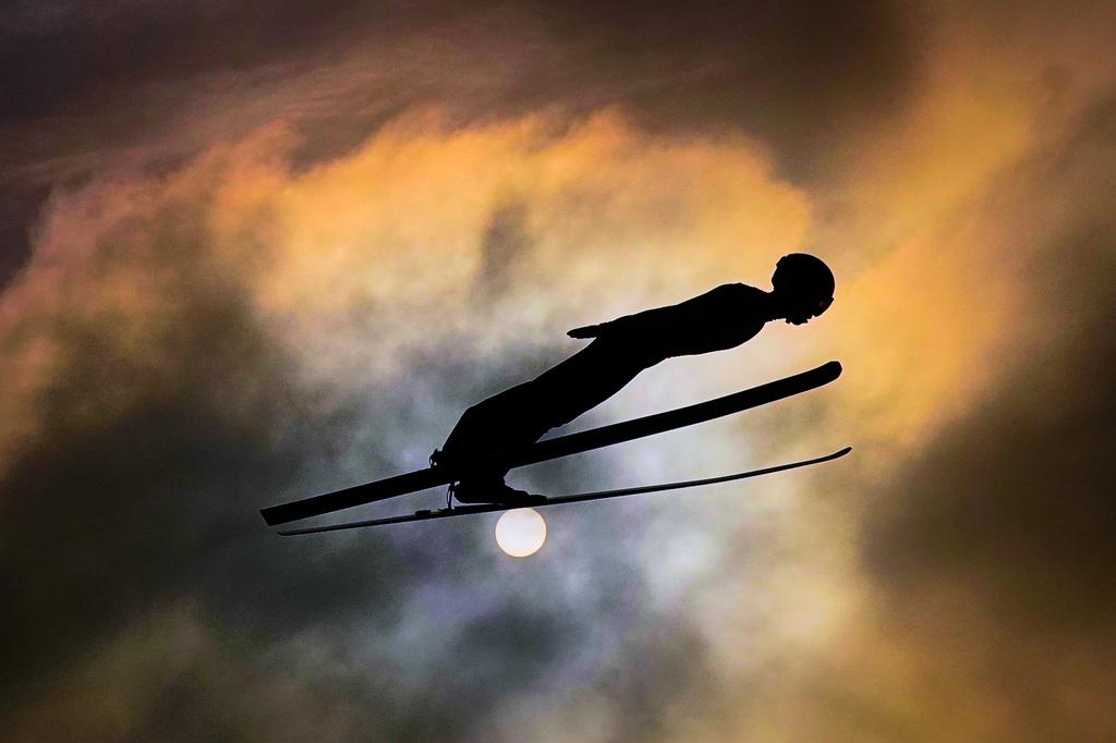 tomasz-markowski-sony-alpha-9-ski-jumper-sideways-on-against-an-orange-cloudy-sun