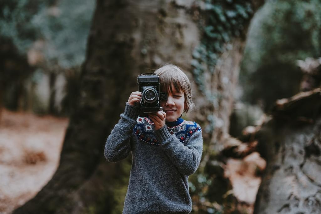 Annie Spratt_Child holding vintage camera
