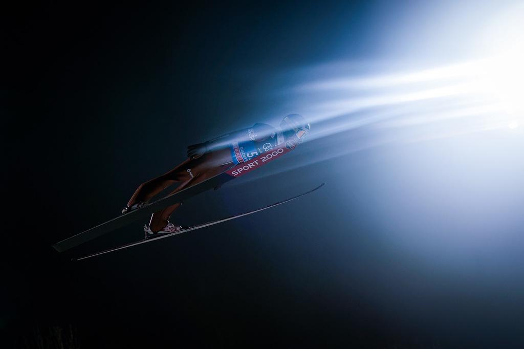 tomasz-markowski-sony-alpha-9-ski-jumper-against-a-dark-sky-flying-towards-a-bright-flared-sun